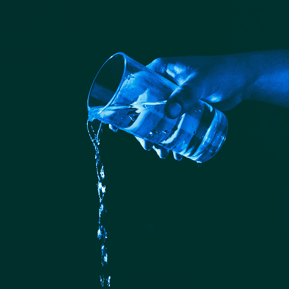 hand pouring glass of water